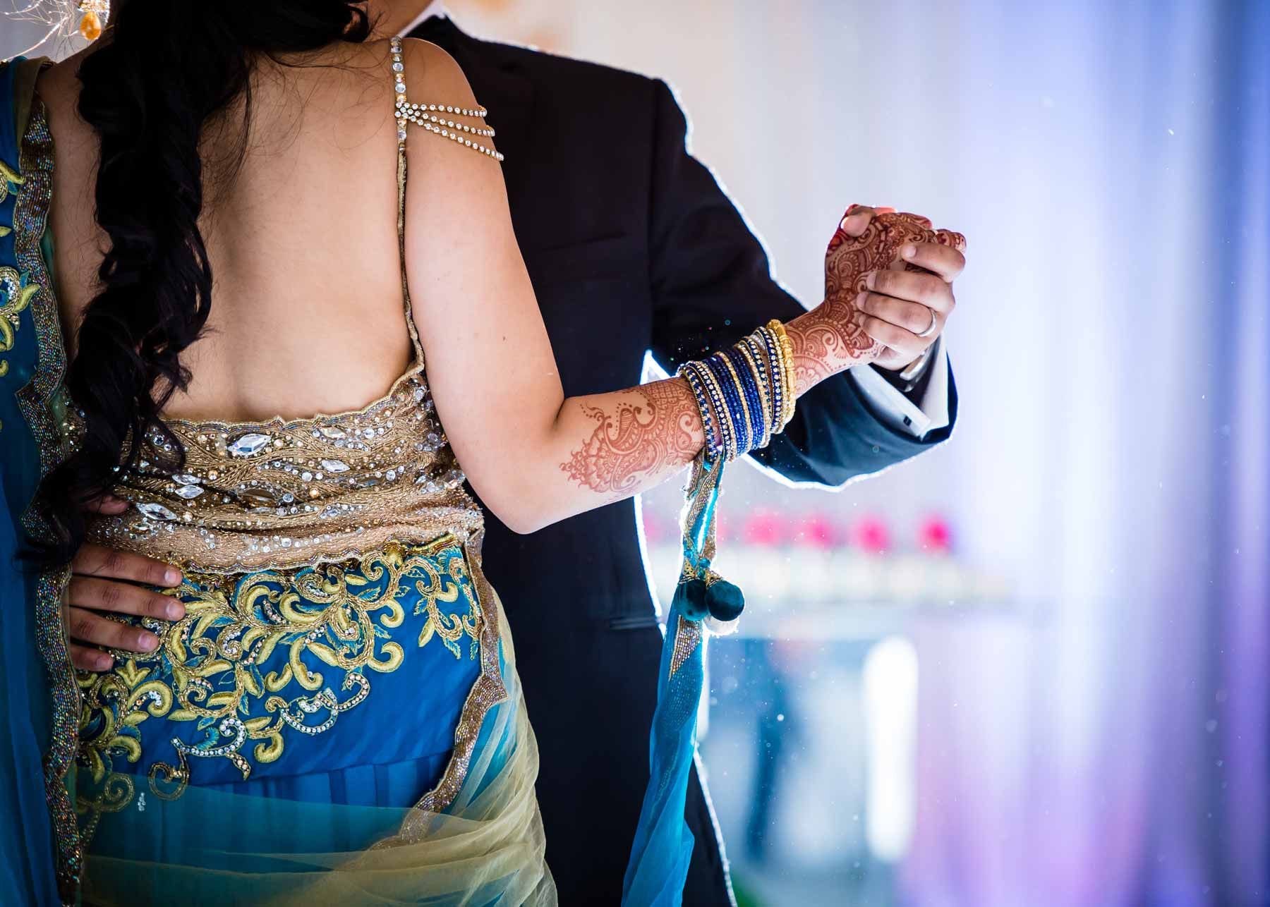 a bride dressed in Indian wedding garments with intricate Henna tattoos on her hand dancing with a man in a black suit