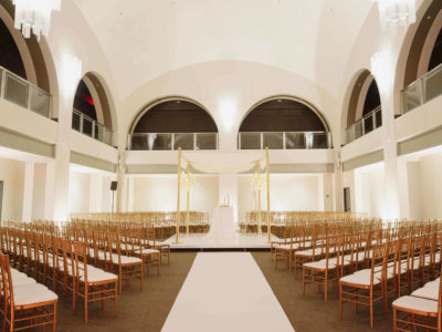 down the aisle of a wedding reception under large arched windows and white decor at arcadian court