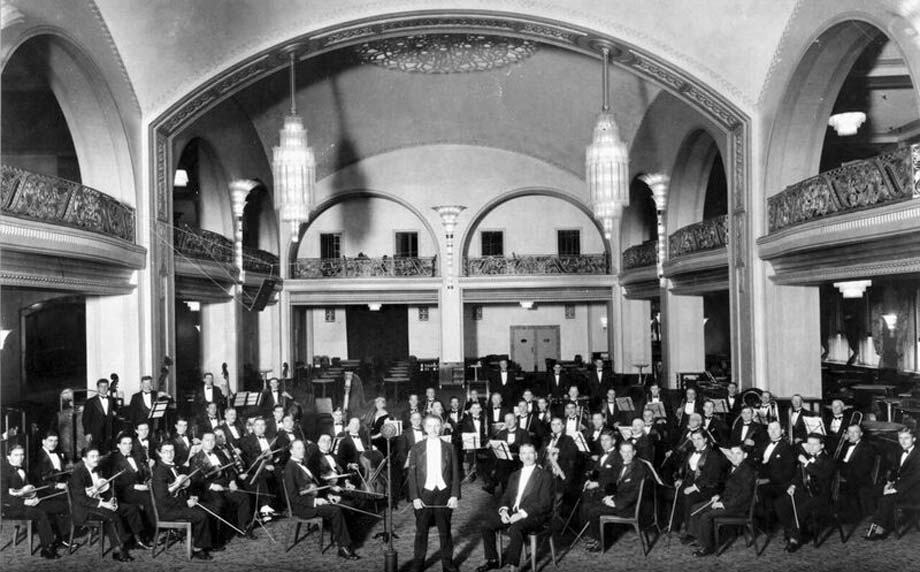 vintage photo of composer and musicians at arcadian court event venue looking at camera