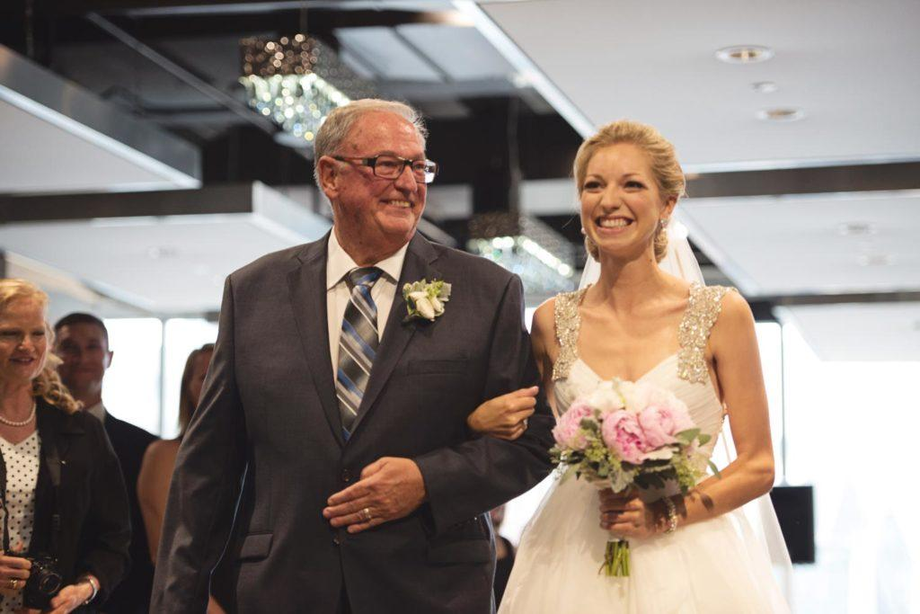 Father of the bride walking the bride down the aisle at a wedding ceremony at Arcadian Loft