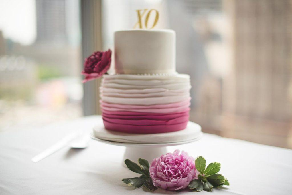 Pink and white wedding cake in front of the windows at Arcadian Loft