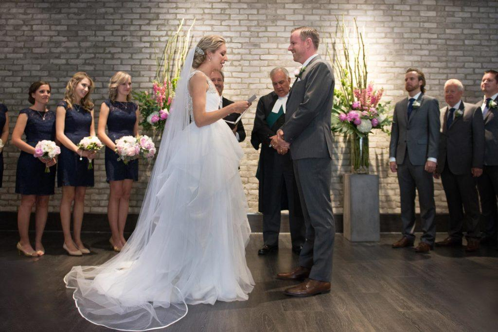 a bride and groom saying their vows during their wedding ceremony
