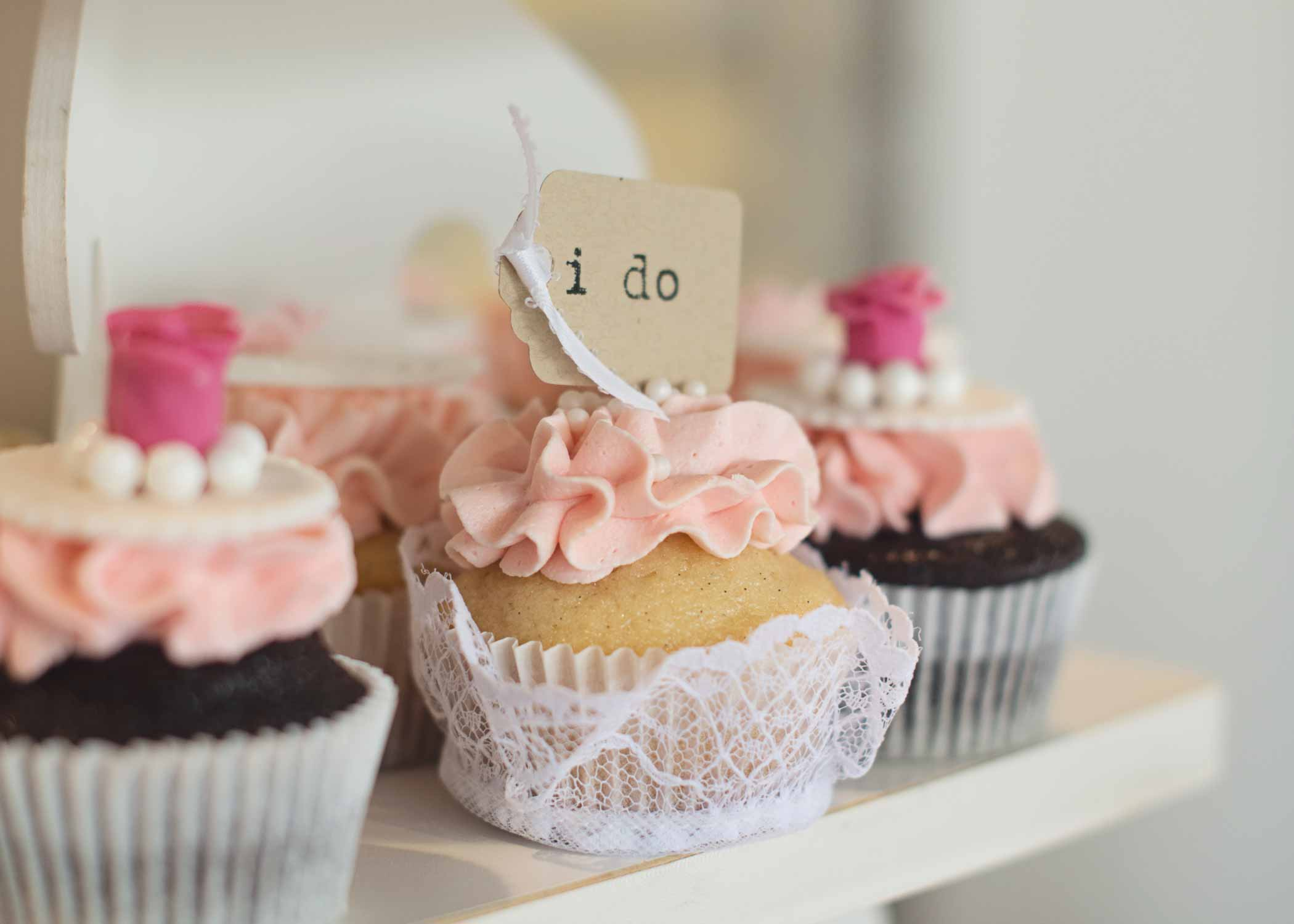 "three shelves of pink cupcakes, one with a craft paper tag saying ""I Do"""