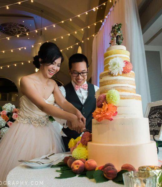 Bride and groom cutting large cake at their wedding ceremony at Arcadian Court
