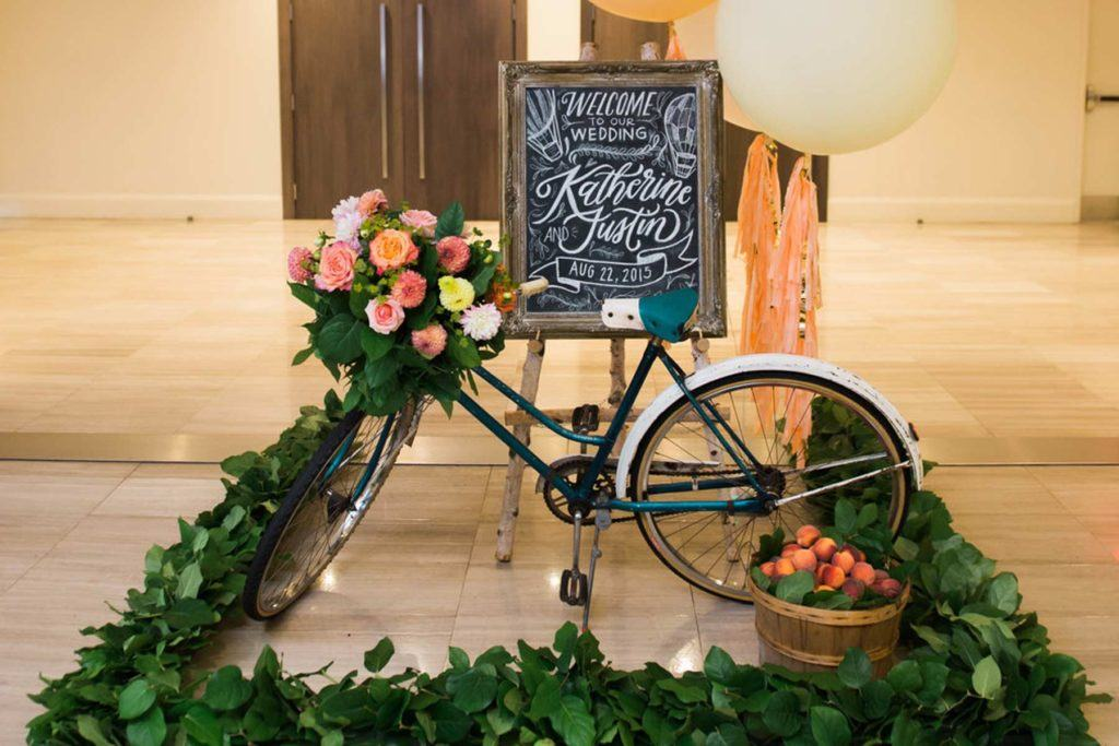 Welcome sign and bicycle at the entrance of a wedding reception in Arcadian Court