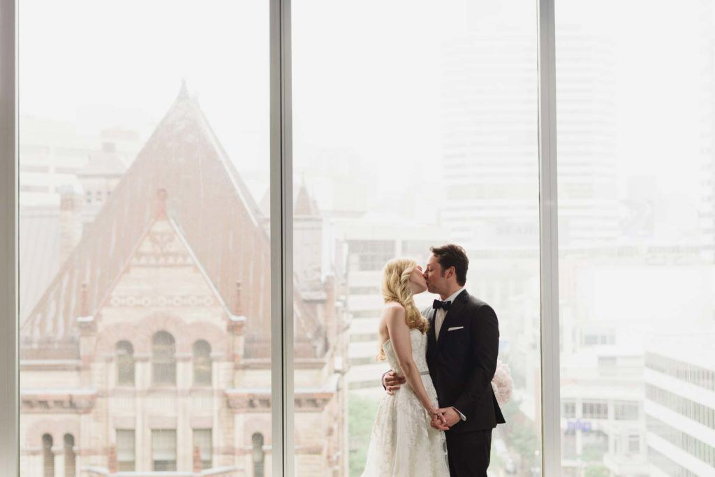 Bride and groom kissing in front of the windows at Arcadian Loft in Toronto