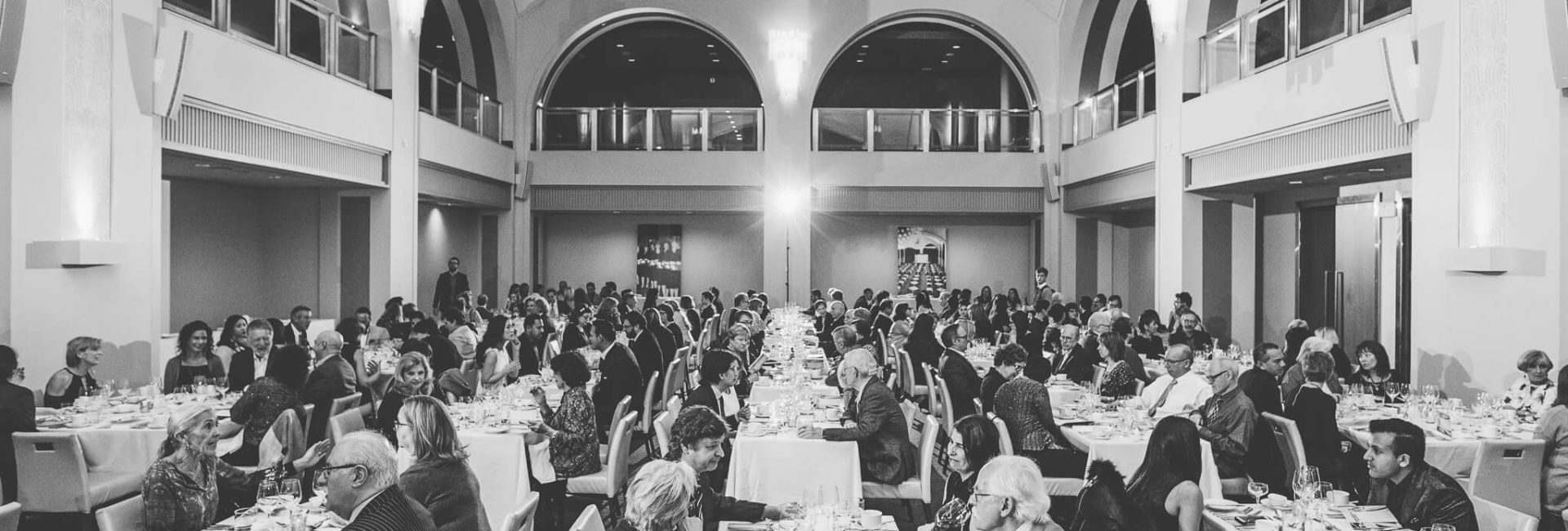black & white photo of several people conversing over dinner in arcadian court event venue