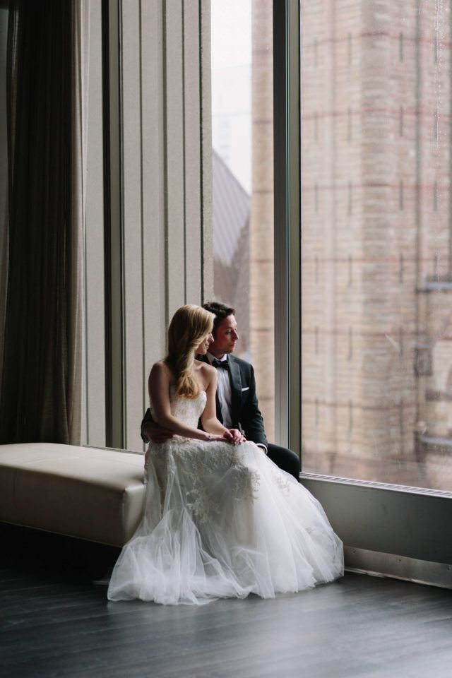 bride and groom sitting by window and arcadian loft