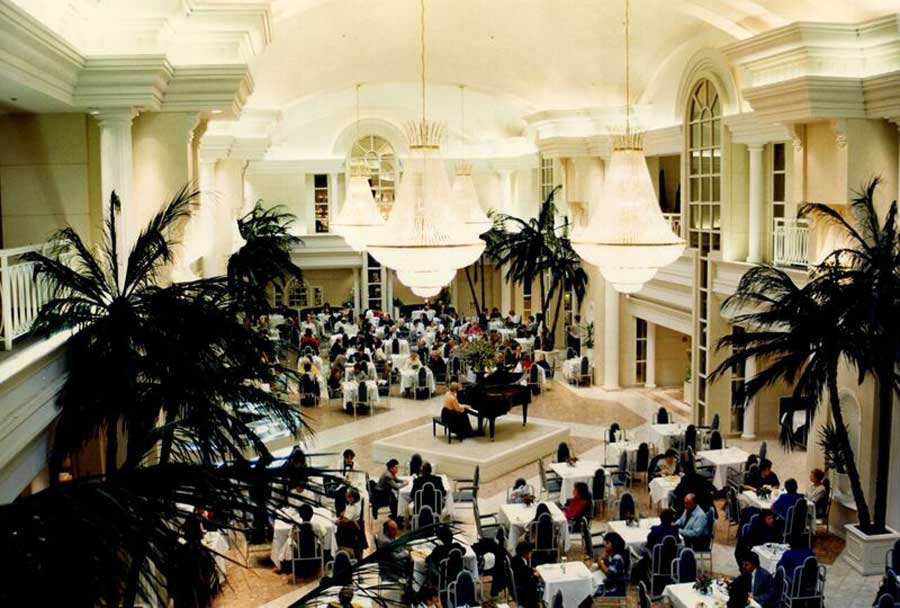 the old arcadian court venue with large crystal chandeliers and a grand piano in the middle of seating