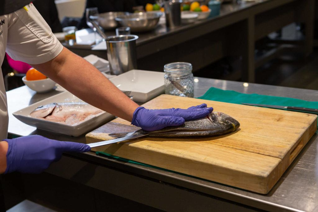 Chef filleting a fish in preparation to make ceviche in Arcadian Studio for a hands-on class