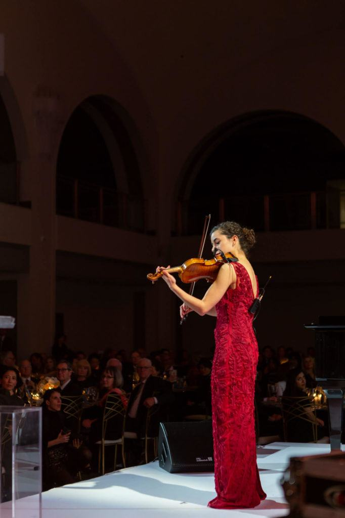 Violinist performing on stage in Arcadian Court in Toronto
