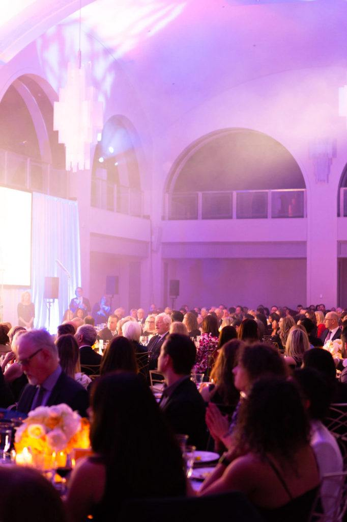 Guests observing a performance at a gala event in Arcadian Court